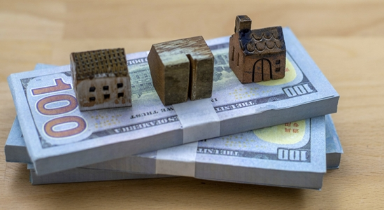 Stacks of money with little houses on top