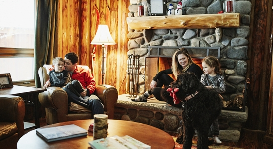 Family sitting around a stone fireplace