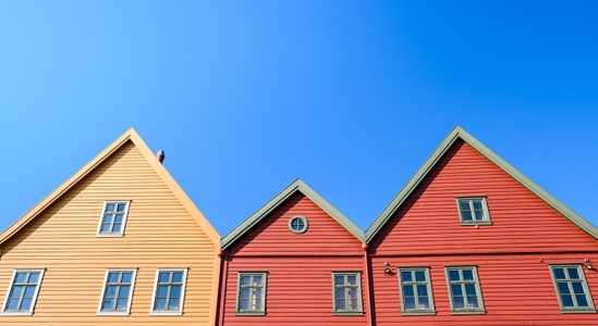 yellow, and 2 red houses against a bright blue sky