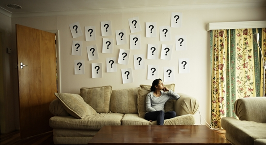 Picture of a lady sitting on a couch with question marks all over the wall behind her