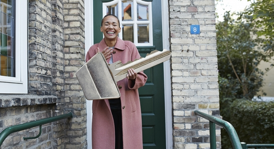Happy Lady with large house key outside of door