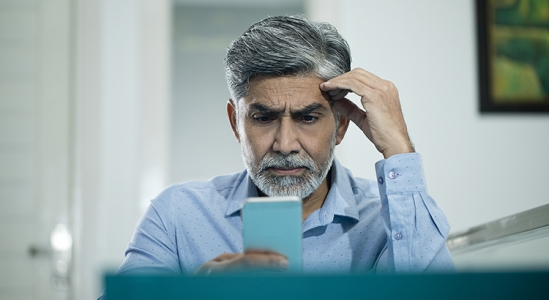 man looking concerned at a calculator